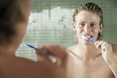 Man Brushing Teeth In Front Of Mirror Stock Images