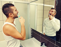 Man brushing teeth and looking at the mirror Royalty Free Stock Image