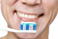 Man brushing teeth toothbrush with toothpaste. Macro closeup Stock Image