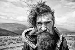 Man with brutal bearded appearance, brutal unshaven man looks untidy. Hipster on strict face with beard looks brutally. While hiking. masculinity concept. Man royalty free stock photo