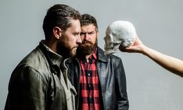 Man brutal bearded hipster looking at skull symbol of death. Overcome your fears. Be brave. Focused on breaking fear. Psychology concept. Human fears and stock photos