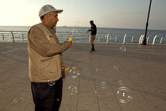 A man with bubbles, Lebanon. A man making bubbles with a bubble want, Lebanon Stock Photo