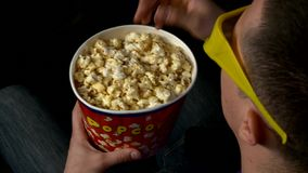 Man with a bucket of popcorn is sitting in a stock video footage