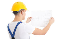 Man builder in blue uniform and helmet holding blueprint isolate. D on white background Royalty Free Stock Images