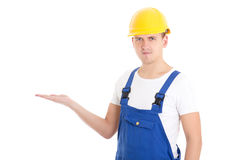 Man builder in blue uniform and helmet holding something on palm. Isolated on white background Stock Photo