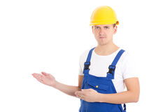 Man builder in blue uniform and helmet presenting something isol. Ated on white background Royalty Free Stock Photos