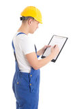 Man builder in blue uniform writing something on blueprint isola. Ted on white background Stock Photo