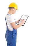 Man builder in blue uniform writing something on blueprint isola Stock Photo