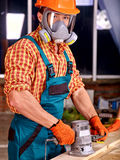 Man in builder helmet. Man worker in builder helmet with electric planer. Indoor Royalty Free Stock Photo