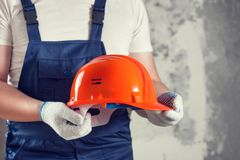 A man builder holds a helmet in his hands. Repair work. Interior decoration of walls Stock Photography