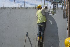 A man builder is installing precast concrete wall structure with steel bar on top floor of building, waring orange safety helmet stock photo