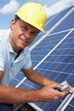 Man builder installing solar panels. Looking at camera Royalty Free Stock Photos