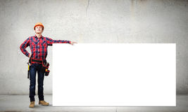 Man builder presenting something Stock Photos