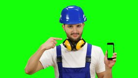 Man in a builder`s suit advertises a smartphone. Green screen. Mock up. Man in a construction suit and a helmet is holding a phone in his hands and pointing at stock footage