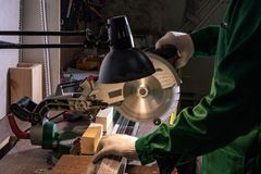 A man builder saws a board with a circular saw in the workshop stock photography