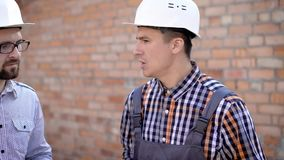 The man the builder in a uniform and gloves shows a brick for the customer in a protective helmet, who came to the stock footage