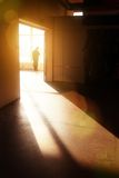 Man in building. Male silhouette in empty interior looking in window, lit by dramatic sunlight Royalty Free Stock Images