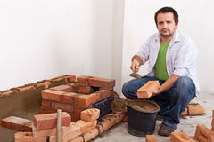 Man building a brick stove or fireplace Royalty Free Stock Photo
