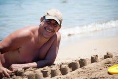 Man building castles on the sand. Handsome man building castles on the sand Royalty Free Stock Photo