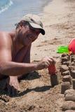 Man building castles on the sand. Handsome man building castles on the sand Royalty Free Stock Images