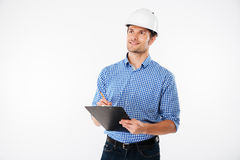 Man building engineer in hard hat writing on clipboard Royalty Free Stock Photography