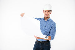 Man building engineer in helmet looking through blueprint. Smiling young man building engineer in helmet looking through blueprint stock photo