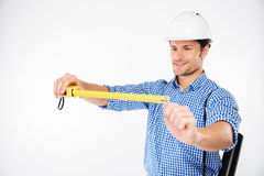 Man building engineer in helmet using measuring tape. Happy young man building engineer in helmet using measuring tape Stock Image