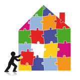 Man building house of puzzle pieces. Silhouette man building house of colorful puzzle pieces Royalty Free Stock Images