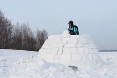 The man building a igloo. The man with a backpack on a snow field building of pieces of snow an igloo in the winter Stock Images