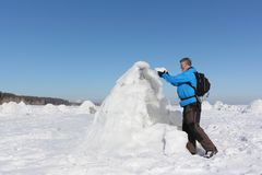 Man building an igloo on a snowy reservoir in winter. Novosibirsk, Russia Stock Photo