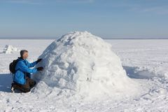 Man building an igloo on a snowy reservoir in winter. Novosibirsk, Russia Stock Photos