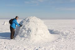 Man building an igloo on a snowy reservoir in winter. Novosibirsk, Russia Stock Images
