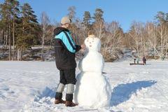 The man building a snowman Stock Photos