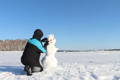 The man building a snowman Royalty Free Stock Photos