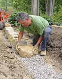 Man building stone wall. On bed of gravel royalty free stock images