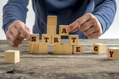 Man building a structure of wooden cubes while assembling word S Royalty Free Stock Photography