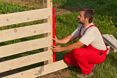 Man building wooden fence. Checking regularly with a spirit level royalty free stock photography