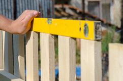 Man building a wooden fence and checking with spirit level. Close up of his hand and the tool in a DIY concept. royalty free stock photos