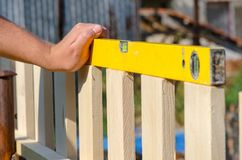 Man building a wooden fence and checking with spirit level. Close up of his hand and the tool in a DIY concept. Man building a wooden fence and checking with royalty free stock photos