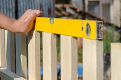 Man building a wooden fence and checking with spirit level. Close up of his hand and tool. Stock Photos