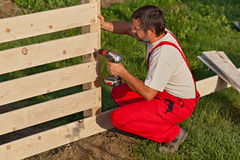 Man building a wooden fence. Fastening the boards with screws royalty free stock photography