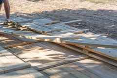 Man building a wooden fence. Workers pick up wooden boards for the fence formwork. Wooden formworks for concrete at construction site stock photo