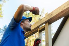 Man is building a wooden house frame Stock Photo