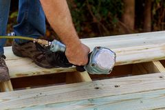 Man building a wooden patio with hammering screwing together beams royalty free stock photos