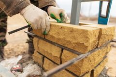 Free Man Builds A Brick Wall At A Construction Site Stock Images - 138731924
