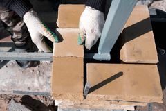 Man builds a brick wall at a construction site stock images