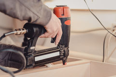 Man builds furniture in the carpentry shop. Man collects furniture details in the carpentry shop. Uses a professional stapler or nail gun Stock Photography