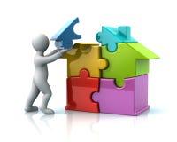 Man builds a puzzle house Stock Photos