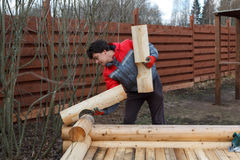 Man builds structure made of logs Royalty Free Stock Images