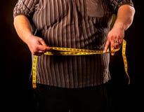 Man bukfett med måttband viktförlust runt om kropp Arkivfoto